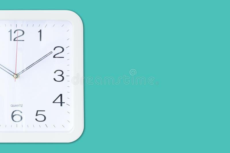 Une horloge murale carrée sur le fond de turquoise photo libre de droits