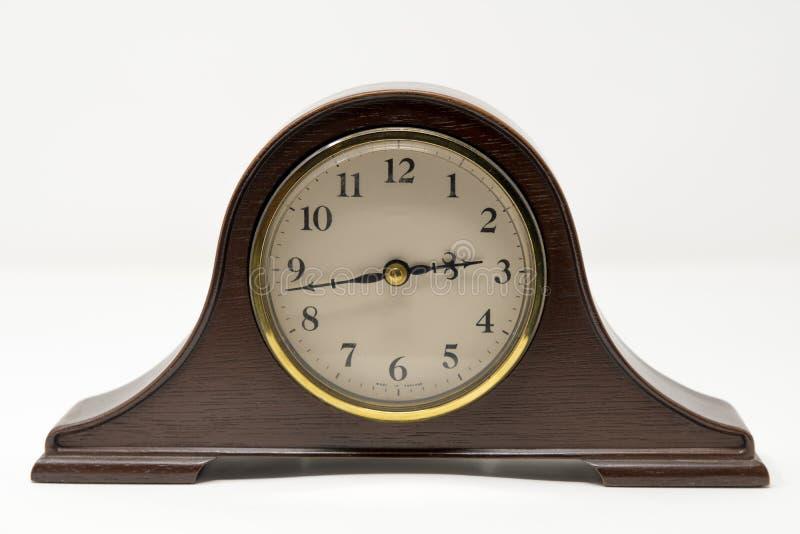 Une horloge traditionnelle de mantel avec de l'or accentue les agains photographiés photo stock