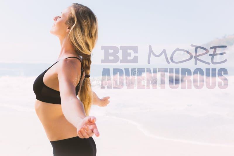 Une image composée de la position blonde d'ajustement sur la plage avec des bras tendus images stock
