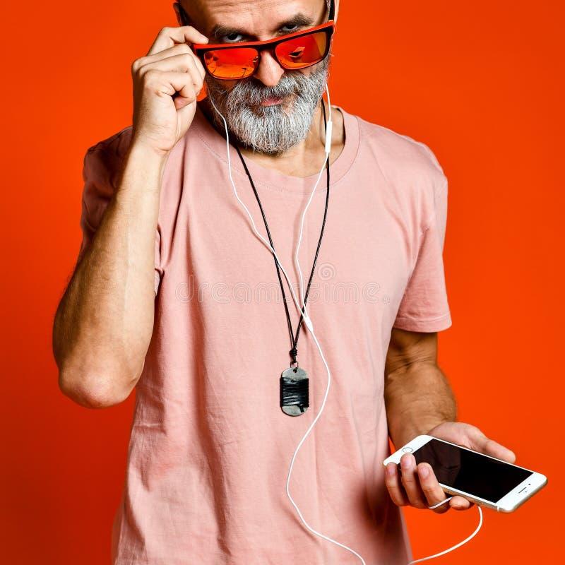 Une image d'un homme plus âgé écoutant la musique avec des écouteurs photo libre de droits