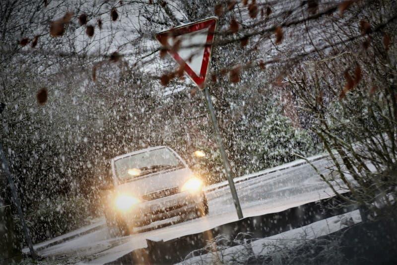 Une image d'une voiture en hiver avec la neige et un poteau de signalisation images libres de droits