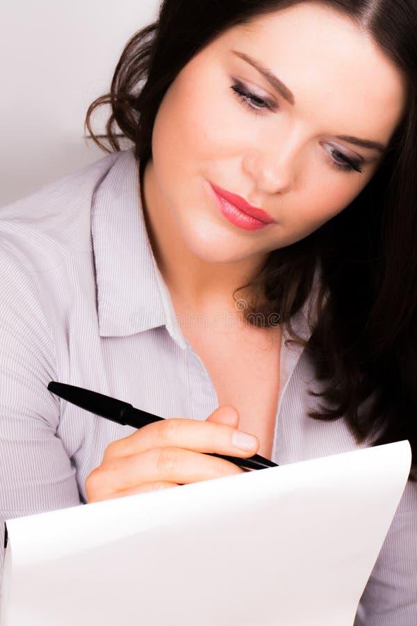 Jeune femelle professionnelle prenant des notes photographie stock