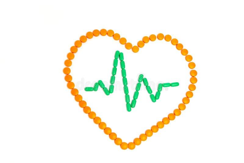 Une impulsion est par les pilules vertes au coeur orange d'isolement sur le fond blanc st?thoscope r?gl? d'argent de m?decine de  images stock