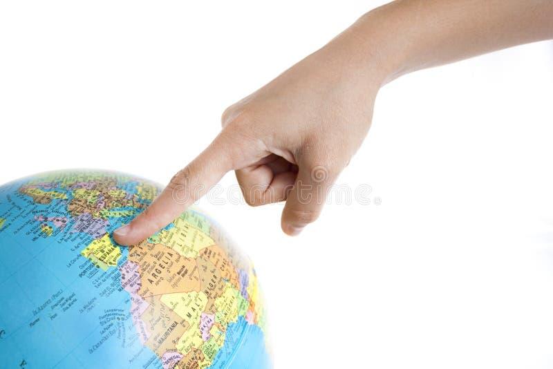 Une indication par les doigts vers l'Espagne dans un globe du monde photographie stock