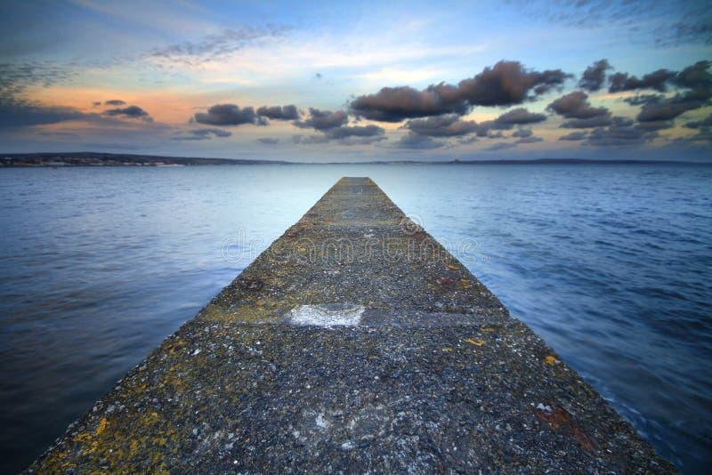 Une jetée abandonnée s'est étendue dans la mer. photo stock