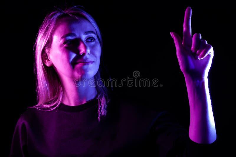 Une jeune belle blonde de fille a accentu? dans bleu et rose des c?t?s soul?ve sa main jusqu'au dessus et appuie sur le bouton de photos stock
