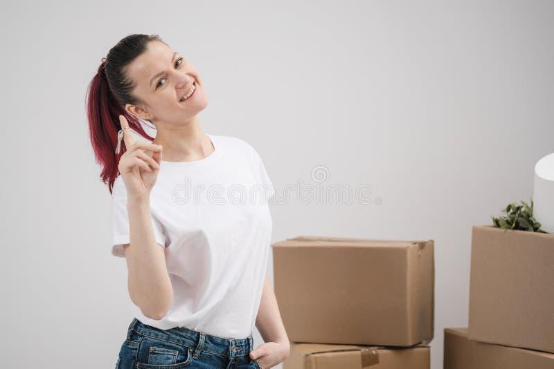 Une jeune belle fille de brune dans un T-shirt blanc tient dans des ses mains les clés sur une nouvelle maison, dans la perspecti photographie stock libre de droits