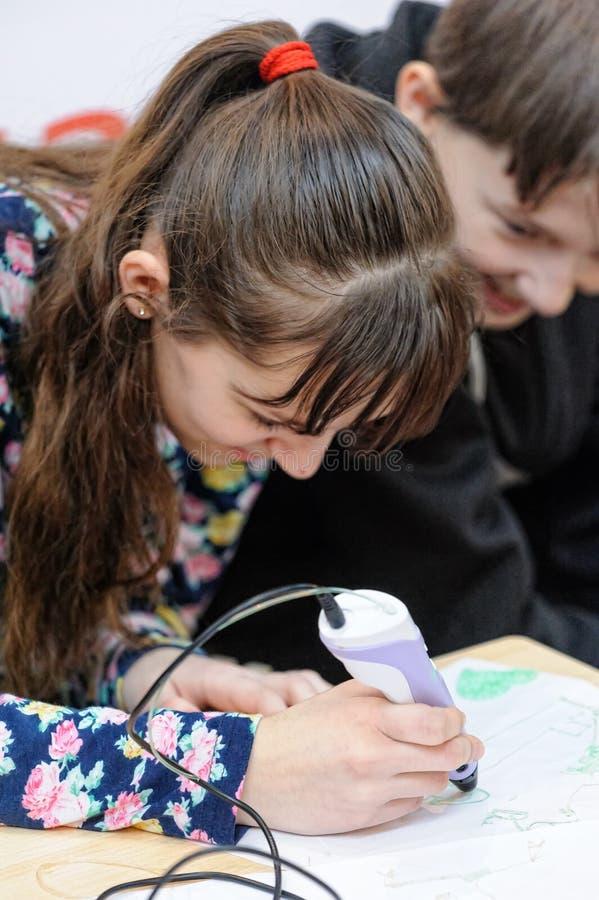 Une jeune belle fille expérimente avec un stylo 3D images stock