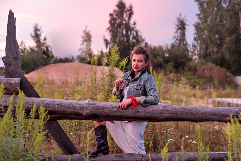 Une jeune cow-girl au coucher du soleil près d'une barrière en bois rustique image libre de droits