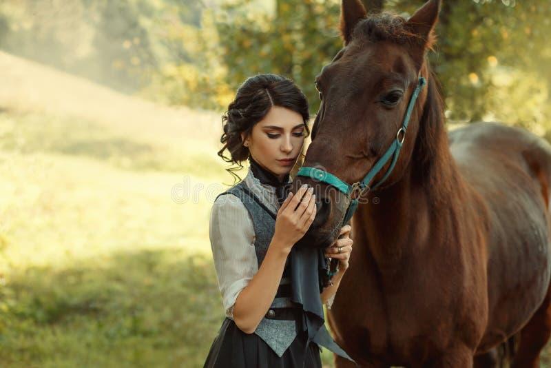 Une jeune dame dans une robe de vintage, avec la tendresse et avec affection étreint son cheval Une coiffure antique et rassemblé images libres de droits