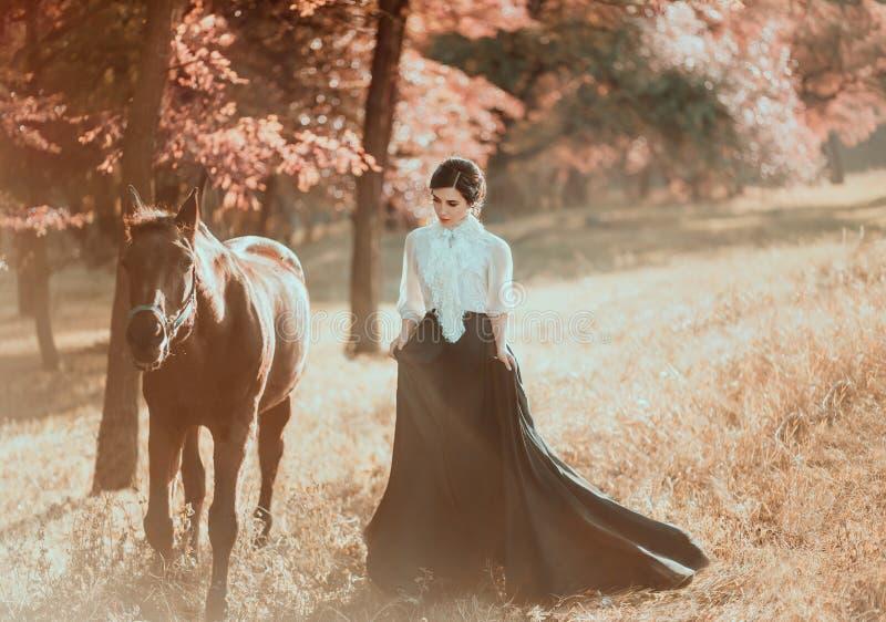 Une jeune dame dans une robe de vintage avec un long train, promenades avec un cheval par les clairières de forêt Un antique, ras photos stock