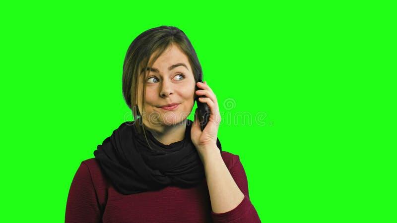 Une jeune dame heureuse parlant au téléphone photo libre de droits