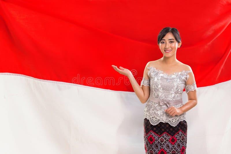 Une jeune dame présentant les gestes, drapeau indonésien à l'arrière-plan photos stock