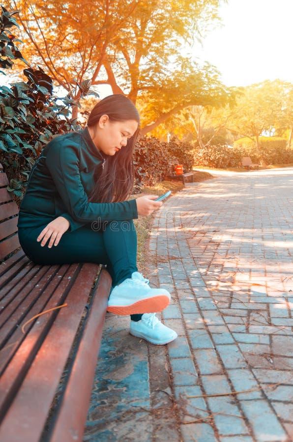Une jeune dame s'asseyant dans un banc photo libre de droits