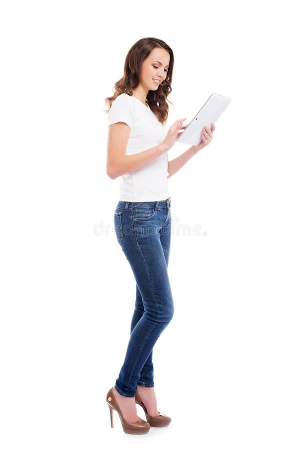 Une jeune et heureuse fille dans des jeans élégants tenant un calcul de comprimé images libres de droits