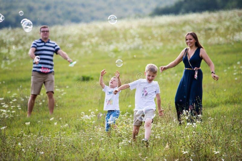 Une jeune famille avec deux petits fils marchant en nature, bulles de savon de soufflement photos libres de droits