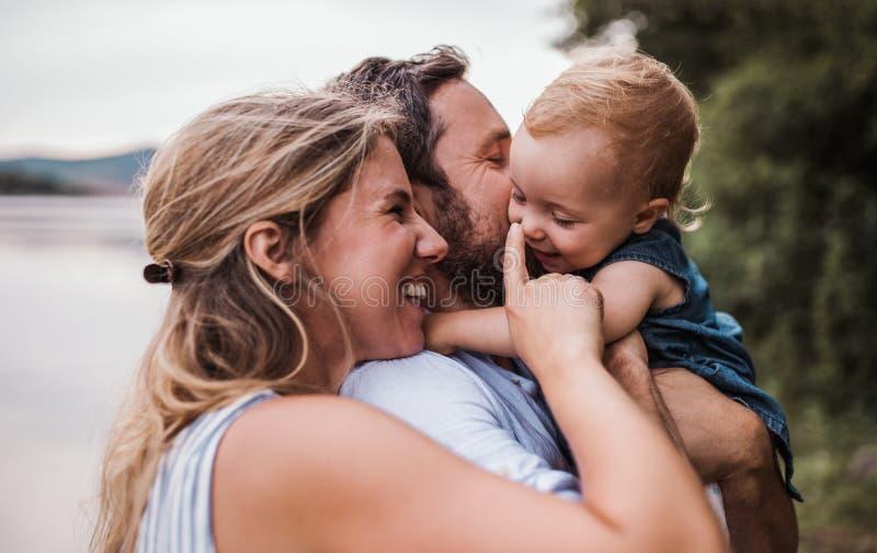 Une jeune famille avec une fille d'enfant en bas âge dehors par la rivière en été images libres de droits