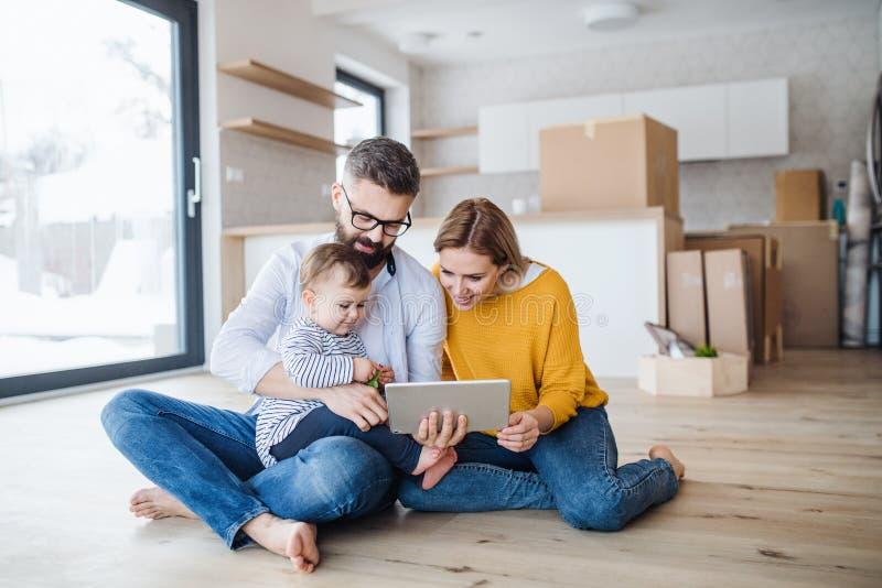 Une jeune famille avec une fille d'enfant en bas âge se déplaçant la nouvelle maison, utilisant le comprimé photos stock