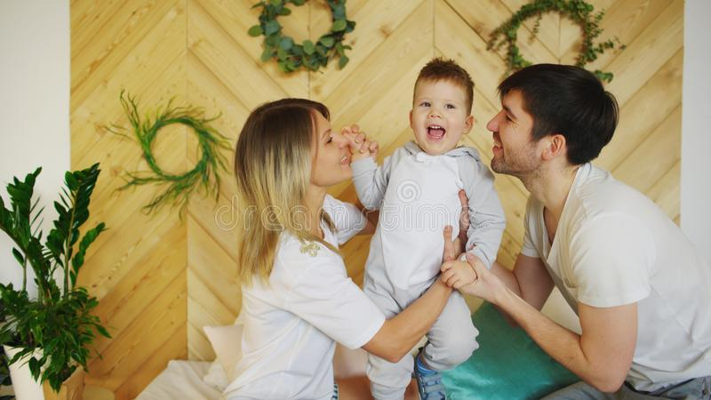 Une jeune famille avec le petit jeu de fils sur le lit dans la chambre à coucher photo libre de droits