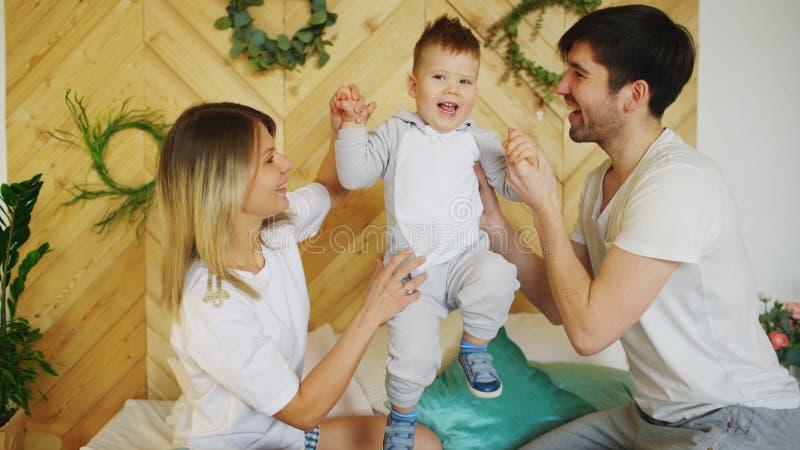 Une jeune famille avec le petit jeu de fils sur le lit dans la chambre à coucher image libre de droits