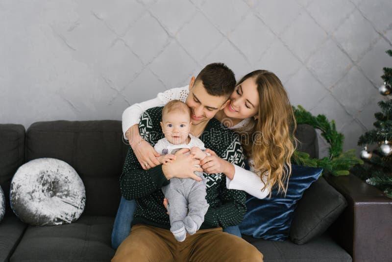 Une jeune famille joyeuse et amicale avec un petit fils enfant assis sur le canapé au sapin de Noël Ils embrassent photographie stock libre de droits