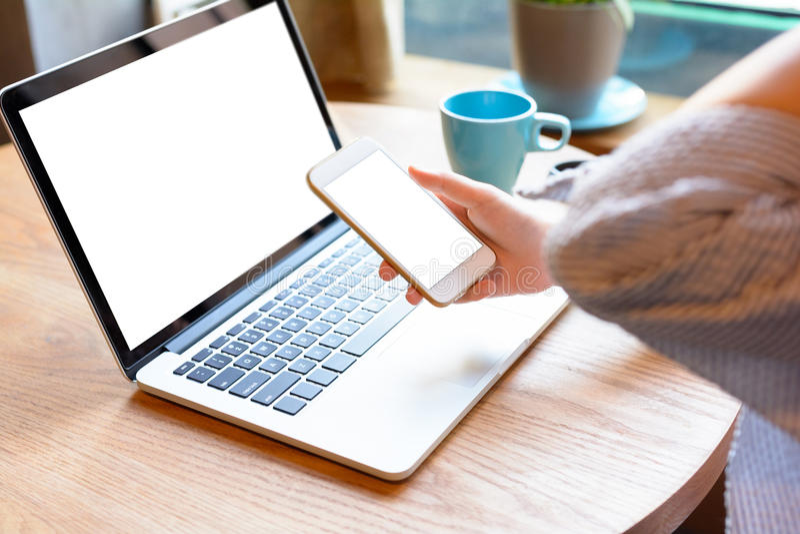 Une jeune femme à l'aide du smartphone et de l'ordinateur portable en café photo stock
