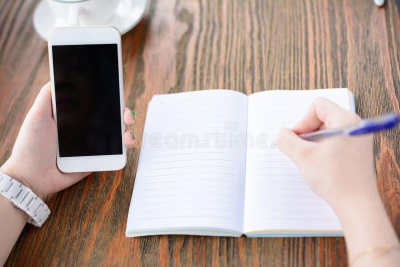 Une jeune femme écrit en café image libre de droits