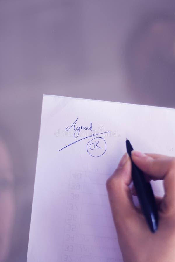 Une jeune femme écrit sur du papier images stock