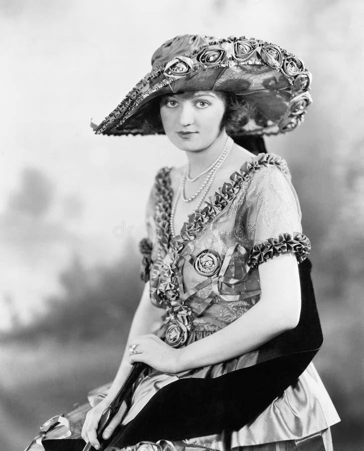 Une jeune femme élégante avec un grand chapeau et une belle robe fleurie (toutes les personnes représentées ne sont plus long auc photographie stock libre de droits