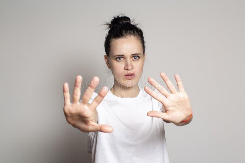 Une jeune femme agitée a proposé ses paumes comme protection, calmant quelqu'un vers le bas et regardant impatiemment la caméra d images stock