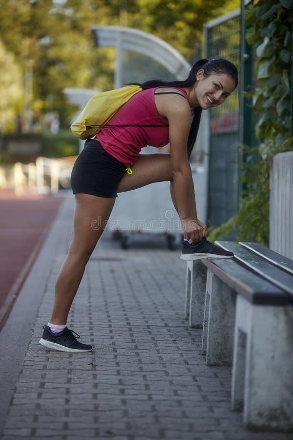 Une jeune femme, 20-29 années, attachant ses dentelles dehors sur un champ de sport, image stock