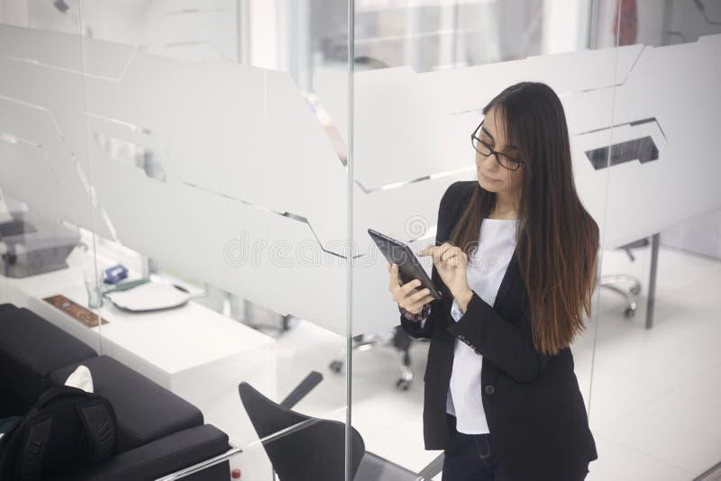 Une jeune femme, 20-29 années, se tenant sur les bureaux modernes à l'intérieur, utilisant le comprimé Vue de côté images libres de droits