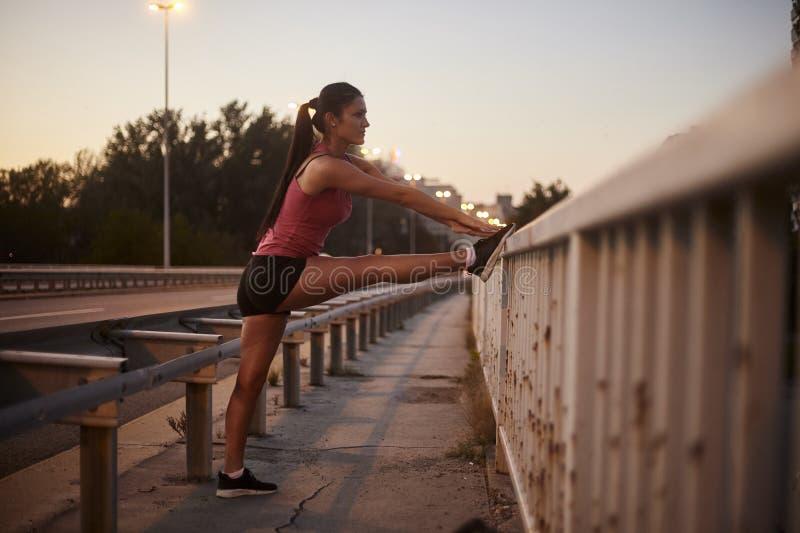 Une jeune femme, 20-29 ans, étirant seules des jambes sur un pont nuit, coucher du soleil image libre de droits