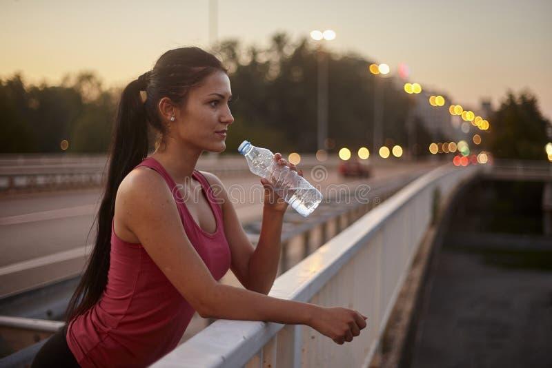 Une jeune femme, 20-29 ans, eau potable de bouteille dehors, habillement de sport photos libres de droits