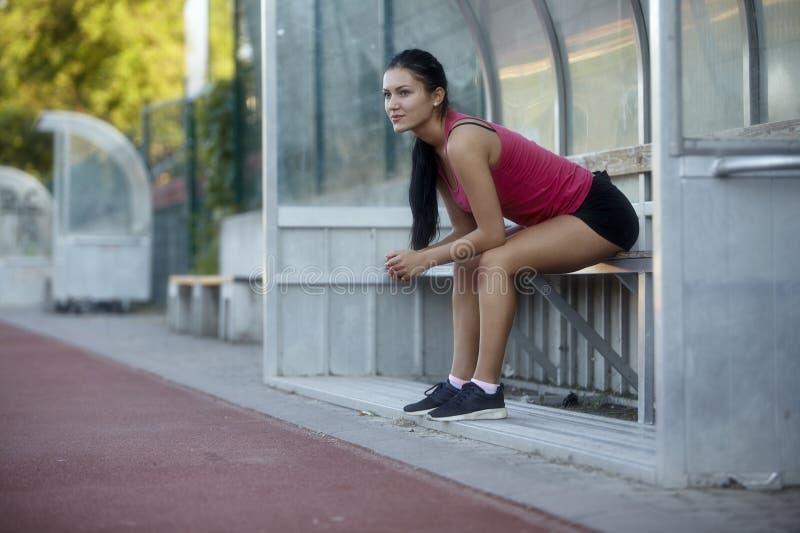 Une jeune femme, 20-29 ans, se reposant tout en se reposant sur un banc aux sports vont au devant dehors photos libres de droits