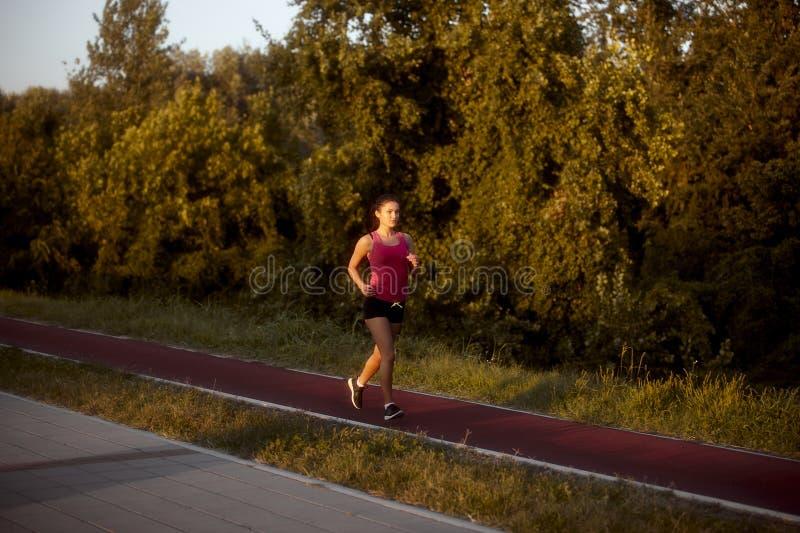 Une jeune femme, 20-29 ans, seul fonctionnant dehors en été, sur une voie fonctionnante de tartan rouge photographie stock