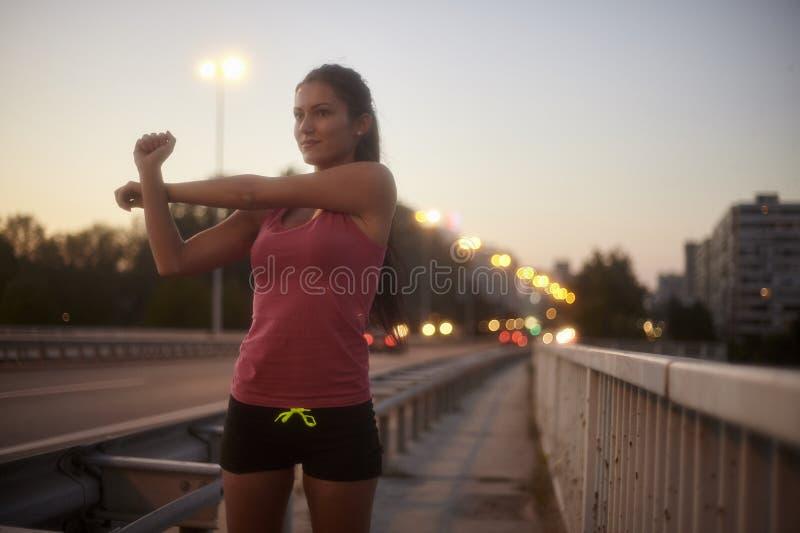 Une jeune femme, 20-29 ans, tir de corps supérieur, souriant d'un air affecté tout en étirant des bras dehors sur un pont photo stock