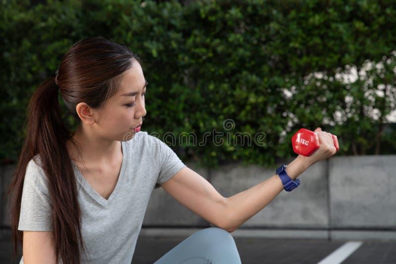 Une jeune femme asiatique se soulevant vers le haut d'un drumbell rouge photo libre de droits