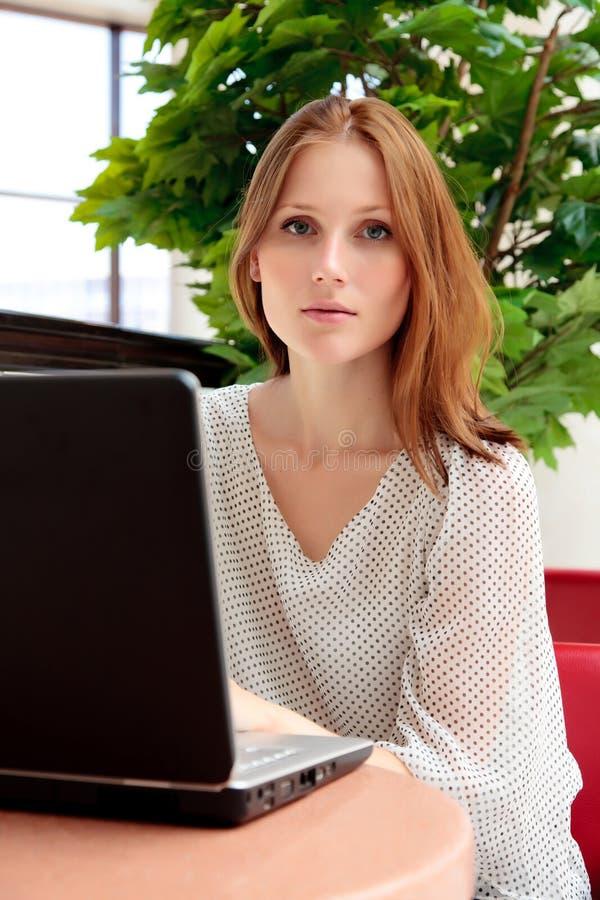 Une jeune femme attirante à l'aide de son ordinateur portatif photos stock