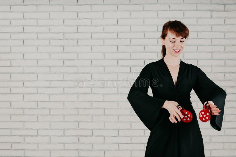 Une jeune femme attirante dans la robe noire, dansant avec castan rouge image libre de droits