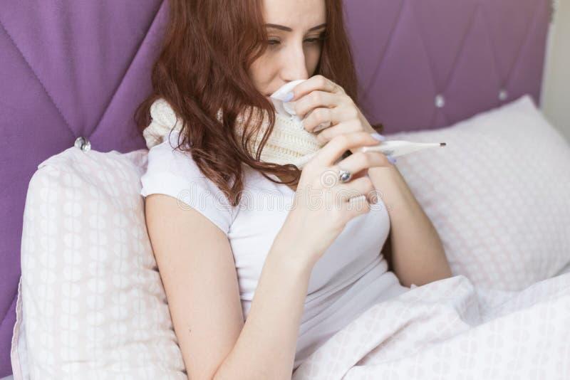 Une jeune femme attirante de brune s'assied dans son lit avec un thermom?tre Froids et traitement ? la maison photos libres de droits