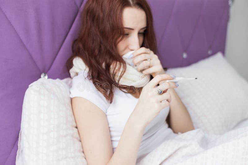 Une jeune femme attirante de brune s'assied dans son lit avec un thermom?tre Froids et traitement ? la maison photos stock