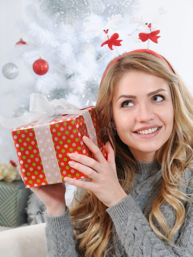 une jeune femme attirante essayant de figurer son cadeau pour chri photo stock image du. Black Bedroom Furniture Sets. Home Design Ideas
