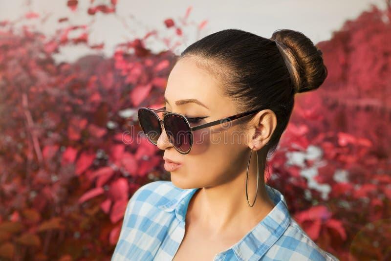 Une jeune femme attirante portant des lunettes de soleil dans une forêt d'automne rouge images libres de droits