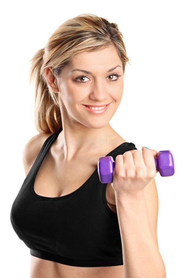 Une jeune femme attirante s'exerçant avec des poids photo stock