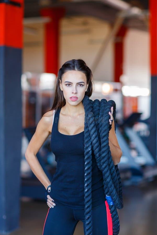 Une jeune femme attirante se tenant à un centre de fitness posant avec une corde physique au-dessus de son épaule photos libres de droits