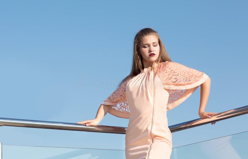 Une jeune femme attirante se tient sur un balcon du ` s d'hôtel sur un fond de ciel bleu Fille merveilleuse des vacances portant  images stock