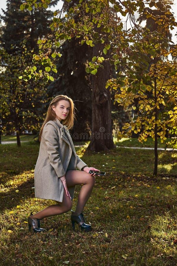 Une jeune femme aux cheveux longs et au manteau en laine en se promenant dans le parc lors d'une soirée d'automne ensoleillée images stock