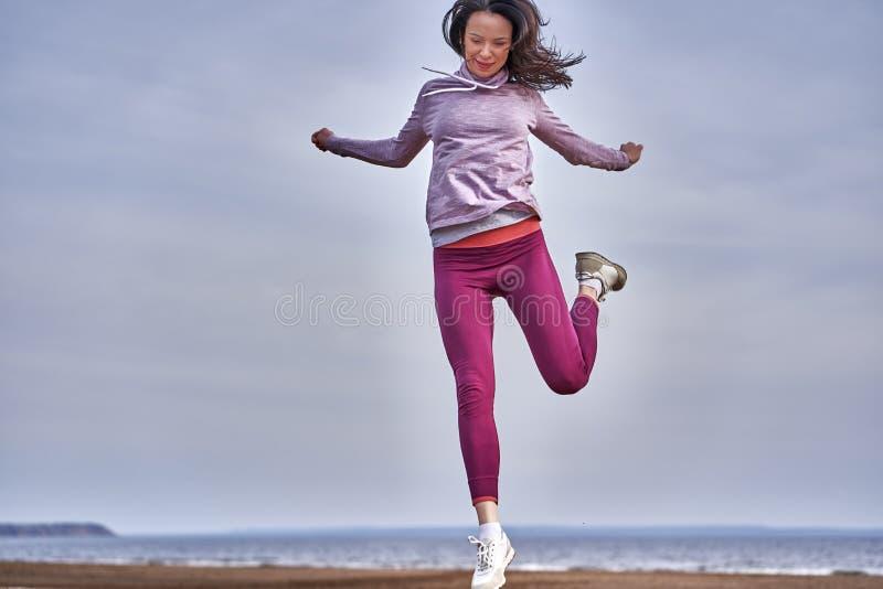 Une jeune femme aux cheveux noirs saute en faisant du jogging Une femme est engagée dans la gymnastique le matin du printemps sur images libres de droits