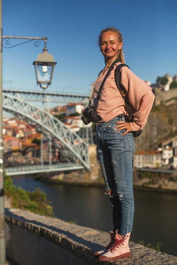 Une jeune femme avec un appareil-photo se tenant devant la rivière de Douro au centre ville de Porto images stock